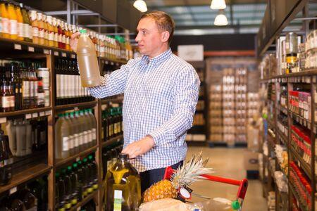 Positive male customer choosing olive oil in supermarket