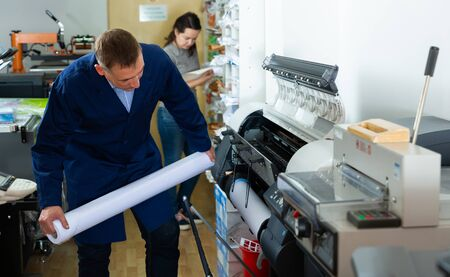 Worker loads new roll of paper into the plotter Foto de archivo