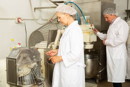 Portrait of two experienced bakery workers watching work of kneading machine making dough Stock Photo