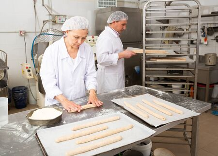 Mature woman professional baker standing at work table and forming dough for baking baguettes Reklamní fotografie