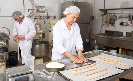 Skilled female baker flattening and shaping dough on floured surface before baking