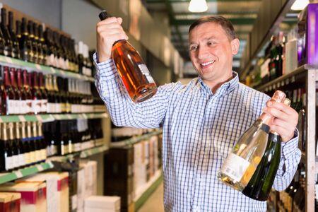 Portrait of happy glad   smiling european man choosing bottle of wine in shop