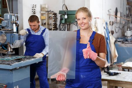 Portrait of successful female glazier posing in glass factory with glass in hands
