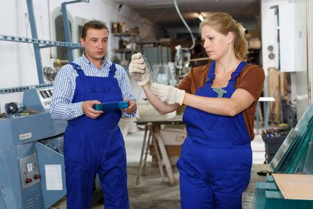 Young woman and her male colleague busy working in glass workshop