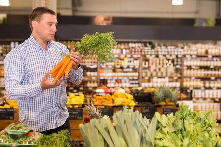 Portrait of man choosing carrot in supermarket