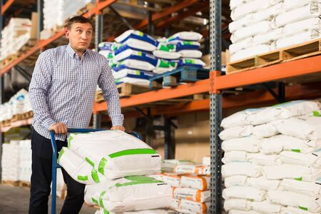 Male buying compost soil for gardening in hypermarket