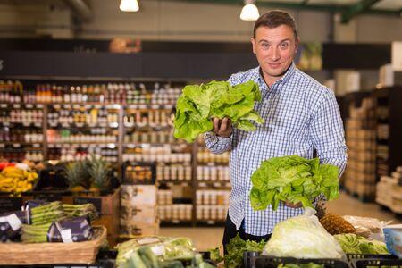 Man choosing fresh greens in supermarket