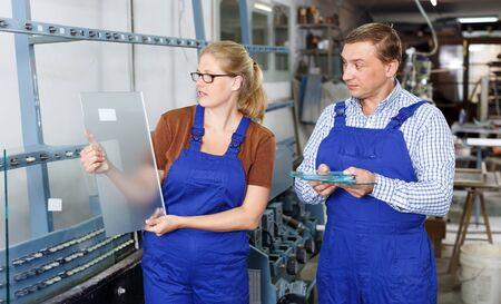 Woman and her male colleague busy working in glass workshop Reklamní fotografie