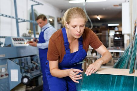 Experienced young workwoman working with glass in industrial workshop