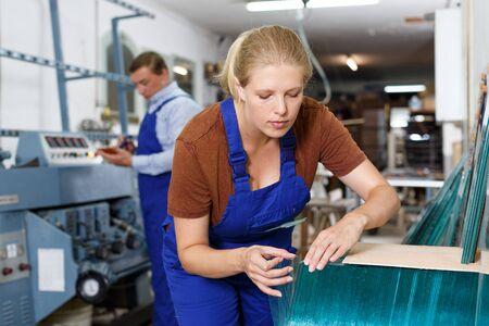 Erfahrene junge Arbeiterin, die mit Glas in der Industriewerkstatt arbeitet
