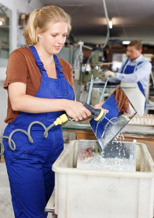 Young attractive woman working in glass workshop, washing glass after cutting