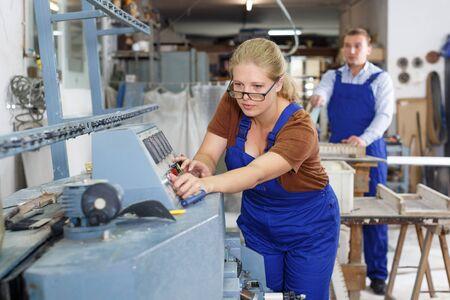 Confident female glazier working on glass straight line bevelling machine in workroom