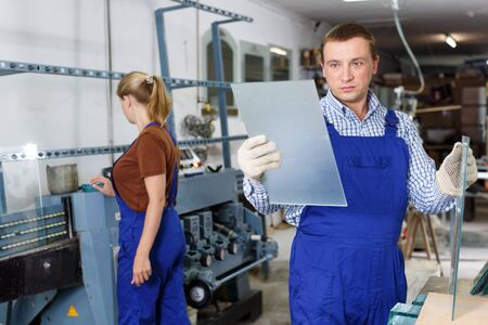 Qualified workman working with glass in industrial workshop