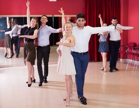 Young smiling people practicing passionate samba in dance class Stock Photo