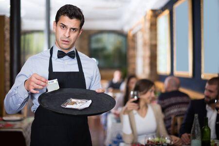 Shocked waiter keeps money to order in a restaurant