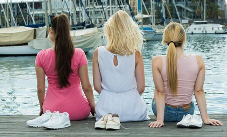 Three young girls sitting on wooden jetty and looking on boats in european marina