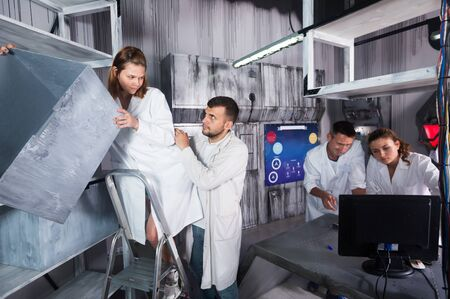 Company of five adults trying to solve conundrum in escape room in view as abandoned lab Stock Photo
