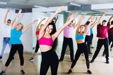 Happy cheerful positive men women performing modern dance in fitness studio Archivio Fotografico