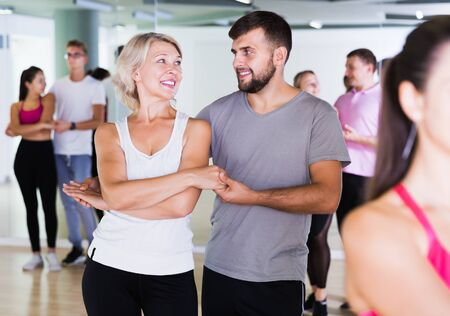 Group of positive smiling young adults dancing salsa in club