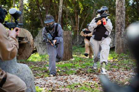 Group of people in full gear playing paintball on shooting range Imagens