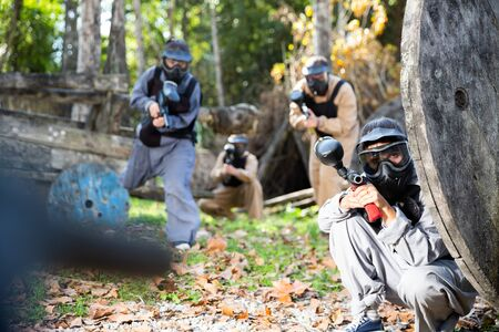 Men and women in protective uniform playing paintball on shooting range Imagens