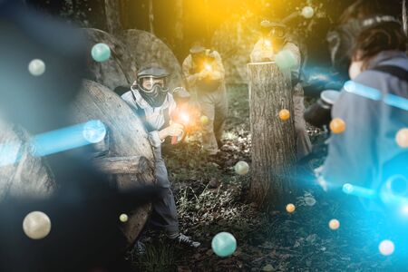 Adult paintball players of opposite teams playing in shootout outdoors, image with light effects Imagens
