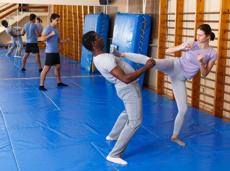 African American man and Caucasian woman training in pair at self protection workout