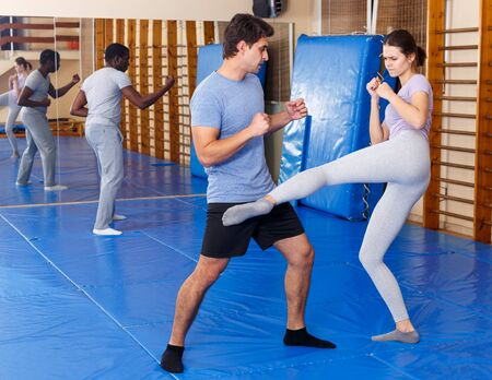 Woman and man practicing self defense techniques in gym