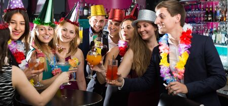 Portrait of women and men in caps with cocktails in the night club