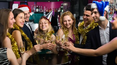 Portrait of positive females and males in caps and garlands in the night club