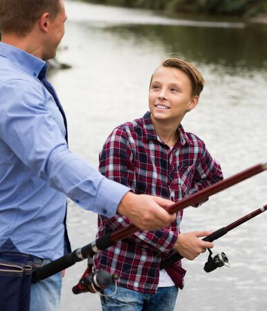 Happy boy fishing with man on freshwater lake on forest