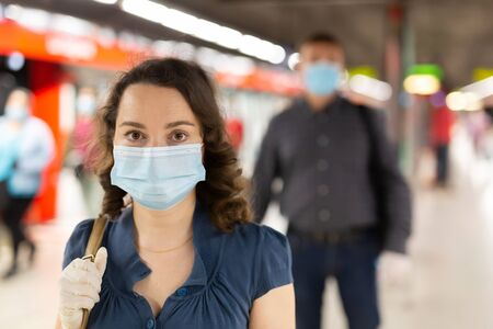 Young brunette in medical mask and protective gloves waiting for subway train at underground station. Necessary precautions during coronavirus pandemic
