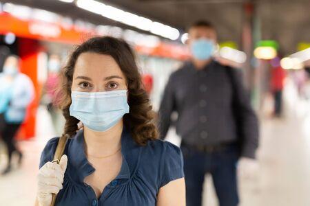 Jeune brune en masque médical et gants de protection en attente d'une rame de métro à la station de métro. Précautions nécessaires pendant la pandémie de coronavirus