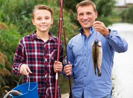 Portrait of cheerful teenage boy and his father holding taken freshwater fish in hands