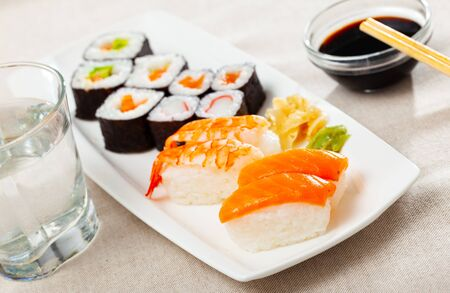 Set of assorted sushi maki and nigiri served with wasabi and soy sauce on white plate