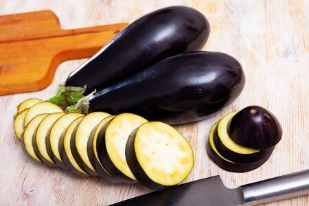 Whole and sliced fresh aubergines on wooden table. Healthy nutrition concept
