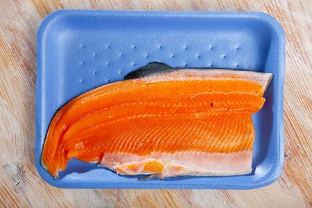 Top view of fresh raw trout fillet on blue plastic tray. Cooking ingredients Фото со стока