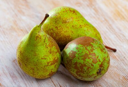 Closeup of fresh ripe pears on wooden surface. Organic fruits concept