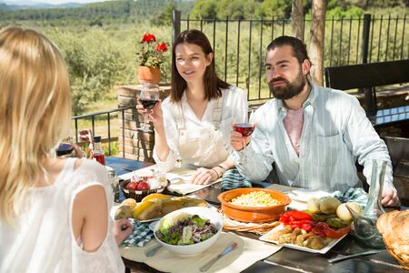 Cheerful carefree young adults spending time together during dinner outdoors in vacation home