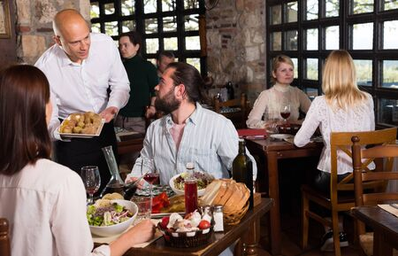 Hospitable owner of rustic restaurant serving traditional meals to guests Stockfoto