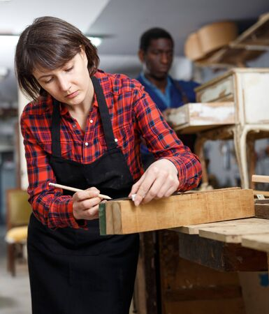 Female restorer working with wooden details in furniture workshop