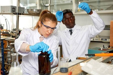 Young woman and man scientists working in research laboratory performing experiments