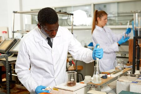 Focused man lab technician in gloves working with reagents and test tubes, woman on background