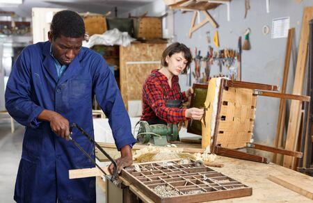 Portrait of male and female restorers working with wooden furniture in workshop Zdjęcie Seryjne