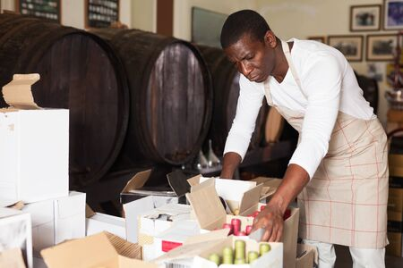 Confident male winemaker inspecting wine bottles in boxes in wine shop