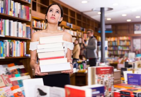 Portrait of glad girl with stack of books in hands in bookshop