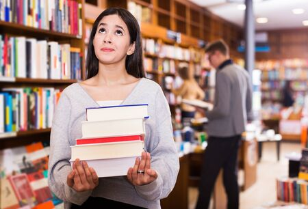 Sad young Brazilian girl holding pile of books in bookstore
