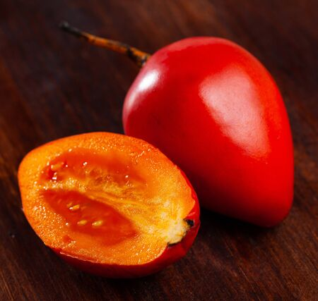 Whole and half fresh red tamarillo on wooden table. Healthy vegetarian ingredient