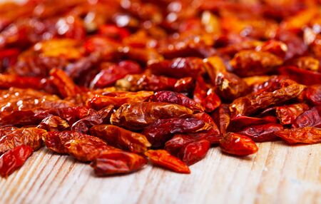 Closeup of dried pungent cayenne peppers on wooden table with copyspace