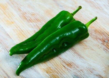 Whole fresh green chili peppers on wooden table. Vitamin cooking ingredients
